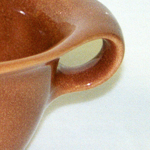 "Tapering cylindrical body,  flaring shaped mouth with spout and circular closed-loop handle; ""nutmeg"" brown glaze."