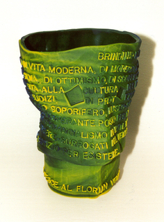 Vase in form of irregular inverted cone in tones of green, blue and yellow with roughly oval mouth, shaped wall and circular base; upper section of wall cast with Italian words running in a continuous spiral starting at top; lower section with one line of Italian encircling base above foot ring.