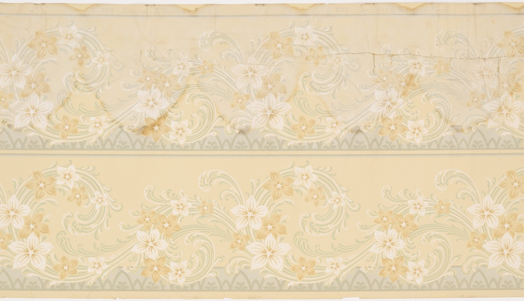 Two bands of continuous swirling vine and flower pattern, each bordered on the bottom by a repeating pattern of alternately large and small inverted curved v's with the large ones containing a simple flower design on a solid ground bordered and separated by thin horizontal bands. Printed in yellow, mica, gray, brown and tan.
