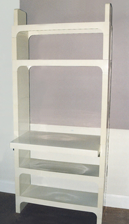 Upright rectangular unit constructed of modular white planar components consisting of two shelves above a desktop and two shelves below, all with upright supports between; two feet as base.