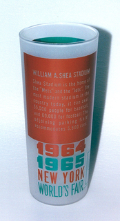 """Tall, slightly tapering cylindrical form of clear """"frosted"""" glass with aqua and brown enamel decoration showing the William A. Shea Stadium, """"1964/1965/NEW YORK/WORLD'S FAIR,"""" and Unisphere logo; brown panel with brief paragraph about the stadium on reverse."""