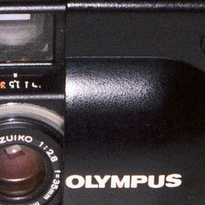 Rectangular black  body with curving edges and sliding panel with slightly raised oval projection in front; panel slides to right to reveal view-finder and lens.  Shutter-button and retractable winding lever on top.