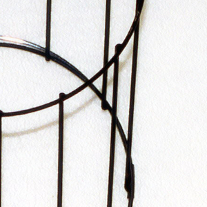 Black-lacquered geometric construction of rigid thin wires forming an angled cylinder.
