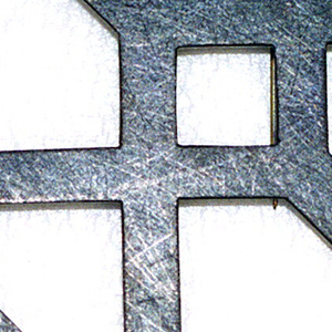 Flat brooch in the form of a cube in outline; dark mat finish.