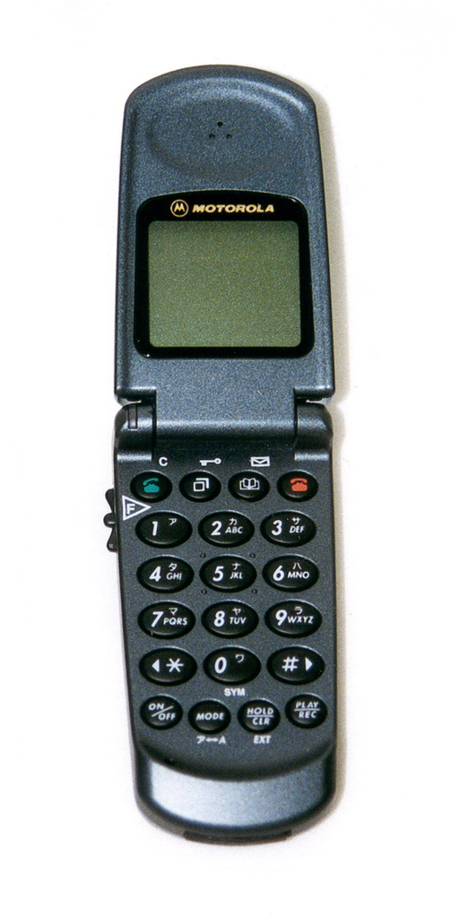 Dark grey body of tapering rectangular form with silver-grey panel on cover and short antenna at top right; hinged cover flips up to reveal earpiece, small display screen, and number/function keypad.
