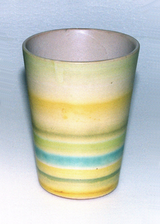 Straight slightly flared beaker decorated around object in yellow, light green, and turquoise.