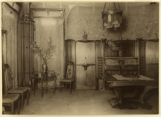 Photograph of the dining room of Hector Guimard's house at 22 rue Mozart. Photograph depicts chairs on the left side, and a table on the right. Cabinets behind the table.