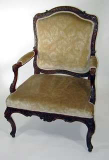 Rectangular upholstered back; posts and rails fully carved with rocaille ornament.  Straight padded arms on curved, carved stumps.  Serpentine front rail, carved similar to back.  Front rail merges into cabriole gadrooned and carved front legs.  Cabriole rear legs.  Upholstered seat and back (yellowish-green, with flowerlike motif).