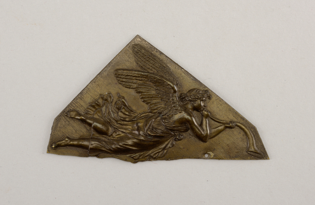 Irregular triangular polygon with repoussé figure of a winged draped female with a horn.