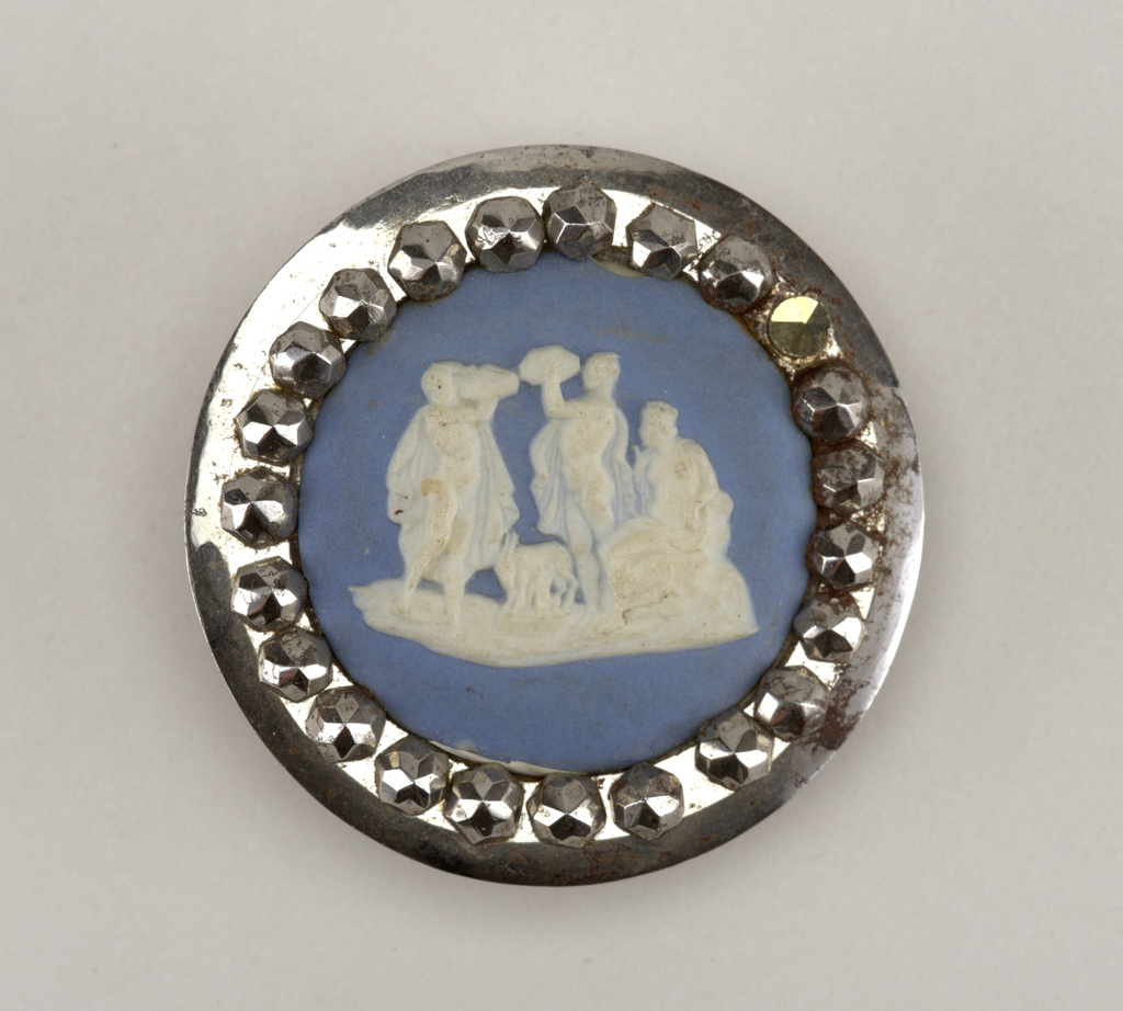 Circular steel frame decorated with twenty-four faceted steel beads, surr- ounding blue and white stoneware plaque. Plaque depicts two standing male nudes, a goat, and a seated female figure, all in white against blue jasperground.