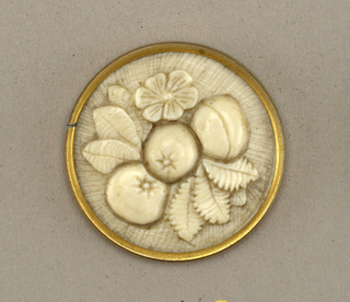 Circurlar button of ivory carved in relief in design of flowers and fruit. Brass shanks.