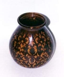 Round vase tapering toward the lip. Brown and orange pomegranate pattern glaze.