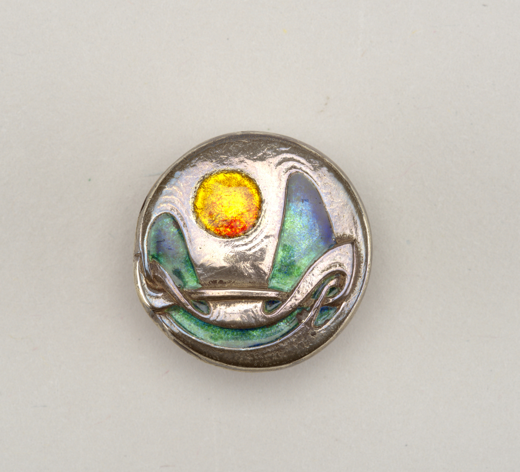 Flat circular silver with soldered loop shank on reverse. Obverse with chased pattern of abstract curves and interlacing, inlaid with green trans-lucent enamel, Recessed circular motif between curves, inlaid with yellow and red translucent enamel.