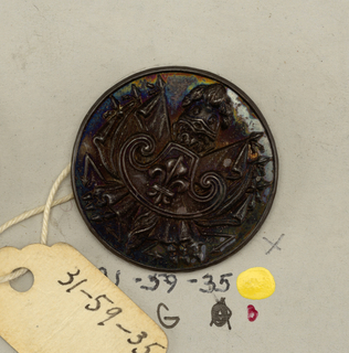 Flat button with ornament of cartouche with fleur-de-lis shown against six crossed flags with four lightning bolts and a helmet with plumes.  Component -a is on card H Component -g is on card 57 Component -h is on card B, was not originally labeled with component