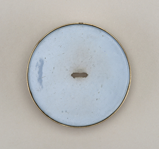 Flat circular button of silver. Rectangular pierced hole in center for attachment. Upper surface enameled in solid pale blue enamel.