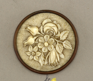 Circurlar button of ivory carved in relief in design of flowers and fruit. Brass shanks.  On card 1