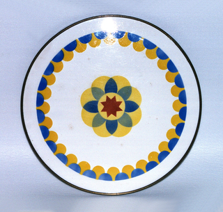 Flat round plate with primary color glaze resembling flower petals on a white ground. Simple metal rim.