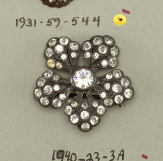 this button is in the shape of five-petalled flowers with rhinestones in the petals and in the centers - two metal shanks are attached to each flower indicating that they are intended for ornament rather than for use as button.  On card 60