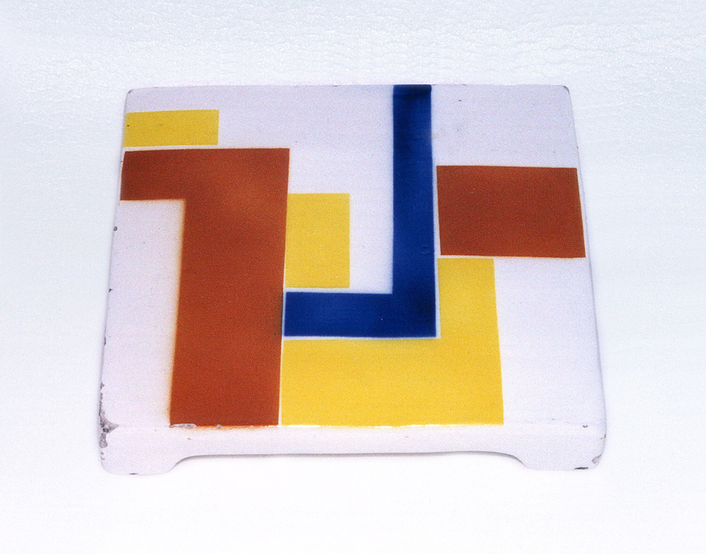 Square trivet raised on four feet, white with red, blue and yellow geometric shapes.