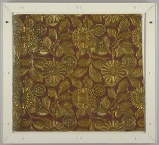 Repeat of leafy stems and rosettes in relief, gold on dull red. One half of each leaf textured with cross-hatching, pebbling, imbrication or venation unlike that of other half. Rosettes centered with Maltese crosses, circles of dots, etc. The metallic-gold floral pattern stands out in high relief from the maroon ground. Nearly square format.