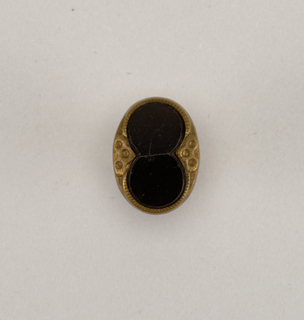oval button in design of brass rim with triangular ornament at either side holding a piece of black glass in shape of a figure 8 - brass back and shank.