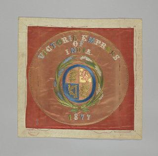 "Circular medallion embroidered with Queen Victoria's coat of arms: a shield divided in four quarters, with the three lions of England in the first and fourth quarters, the lion of Scotland in the second, and the harp of Ireland in the third. The shield is surrounded by sheaves of wheat. At top center is embroidered ""Victoria Empress of India,"" and at botton center ""1877.""  Embroidered in blue, green, brown, white and gold on a peach satin ground."