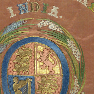"""Circular medallion embroidered with Queen Victoria's coat of arms: a shield divided in four quarters, with the three lions of England in the first and fourth quarters, the lion of Scotland in the second, and the harp of Ireland in the third. The shield is surrounded by sheaves of wheat. At top center is embroidered """"Victoria Empress of India,"""" and at botton center """"1877.""""  Embroidered in blue, green, brown, white and gold on a peach satin ground."""