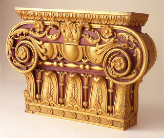 Wood block in the form of a pilaster capital with applied gilt bronze mounts: between narrow leaf and dart molding at top and a wide bottom tongue and flower border is Ionic volute formed of curved metal and terminating on each side in a rosette.  Between the two volutes are egg and dart molding, bead and lozenge molding under acanthus leaves.