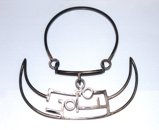 Made of thick squared silver wire; plain circular neck band with horizontal bar at front from which depends curved pendent with triangular side projections, two circles, and other geometric articulations. Clasp at ring joint where neck band and bar meet on one side.