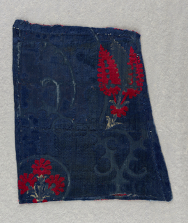 Fragment of a large scale ogee patterned velvet with three colors. The pattern is created by blue cut pile with details in red and white cut pile. The background consisting of a linear pattern is voided. The pile is cut to one height over the entire surface.