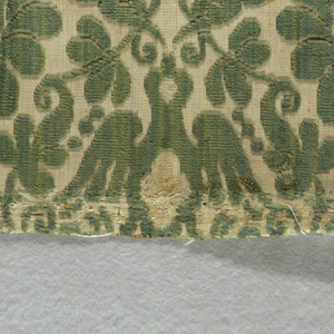 Fragment of woven velvet with a small-scale symmetrical design of a bird, flowers and scrolls in green and pink pile on a white foundation.
