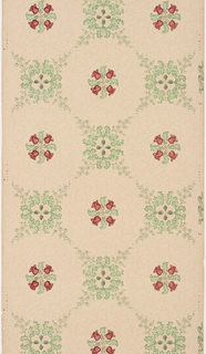 Four red roses alternate with four green leaves to make up the repeated, circular focal point of the sidewall, like a pinwheel. A thick circle of negative space surrounds the roses and leaves. The rose pattern alternates with scrolling green foliage that is also circular. Thin green floral motifs connect the scrolling foliage patterns. Printed on a light tan ground.