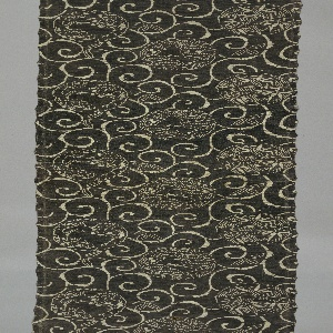 Weft-ribbed tabby ground with large roundels of pine, bamboo or plum scattered in ground of continuous curling arabesques, reserved in white on dark greenish-gray ground.