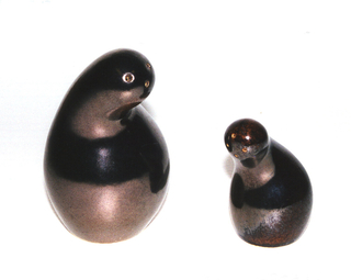 "Gourd-like form (a), having bulbous lower section tapering up to a curved neck; the rounded top with three holes set off-center; cork stopper (b) in bottom.  Lustrous dark bronze ""Gun Metal"" glaze."