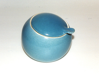 Blue-glazed globular bowl (a) with canted circular mouth; slightly domed circular lid (b) with shaped tab handle on rim. Off-white interior.