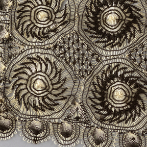Set of lace accessories consisting of a headscarf, two different collars and a pair of cuffs worked in black and white thread. The stretched threads forming the circles are white; the knotted interlacing threads are black.