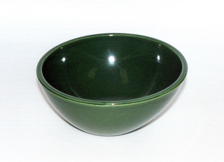 Deep circular bowl rising to a wide canted mouth. Green glaze.