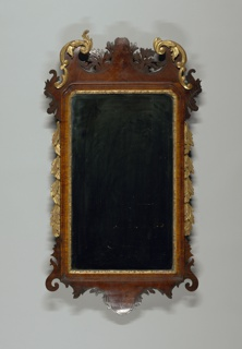 Carved and gilded vertical frame, double arch at top with centered tall pyramid of assymetrical foliage carved a jour and tall curved leaf forms at each corner which flow into serpentine curves and then join straight sides; flowers entwined around straight sides; bottom raid duplicates curve at top rail and has assymetrical group of foliage carved at center. Mirror made in two pieces.