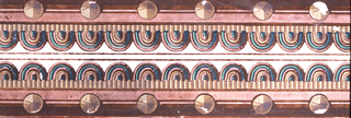 Passementerie design with central cream stripe overlaid at top and bottom by brown repeating shield motif; bordered above and below by wide brown stripes of graduated intensity, overlaid by regularly spaced bosses. Brown stripes are printed in flock.