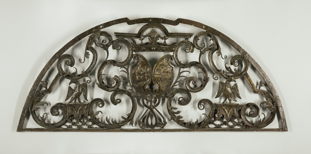 Hemispherical open ironwork in c-shapes and s-curves with vegetal forms. To left and right, birds stand on a platform with a tasseled cloth hung over latticework punctuated with flowers. At the center, two cartouche, each with the initial H.