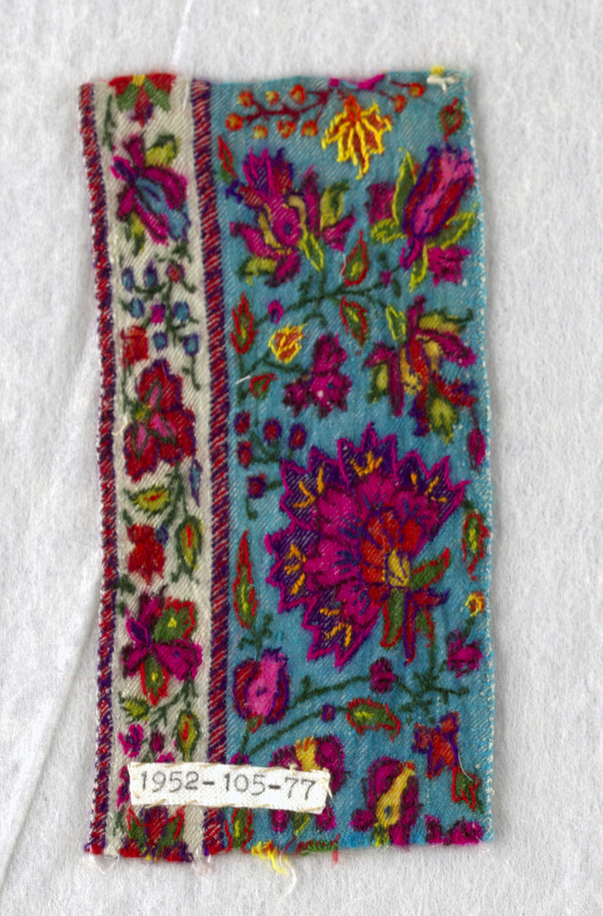 Kashmir shawl fragment. Elaborate flowerheads on scrolling stems with fine small leaves, buds, and small flowers; scrolling floral guard border with decorated guard strips.  In yellows, orange, vermillion, cerise pinks, greens, purples, blue, on bright turquoise ground.  Guard band on white ground.