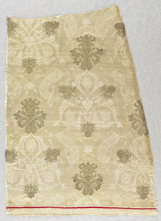 Double warp twill, brocaded in gold (gold beaters' gold).  Patterned with trefoils, each enclosing a rose, flanked at top by diagonal banderoles with debased Islamic inscription, which is arranged in diagonal repeats in cream tabby on cream twill ground.  Metallic brocaded palmettes and brocaded insect. This piece has a red stripe across the bottom, indicating end of piece.