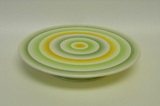 Flat, circular body on a low base with circles of greens and yellow.