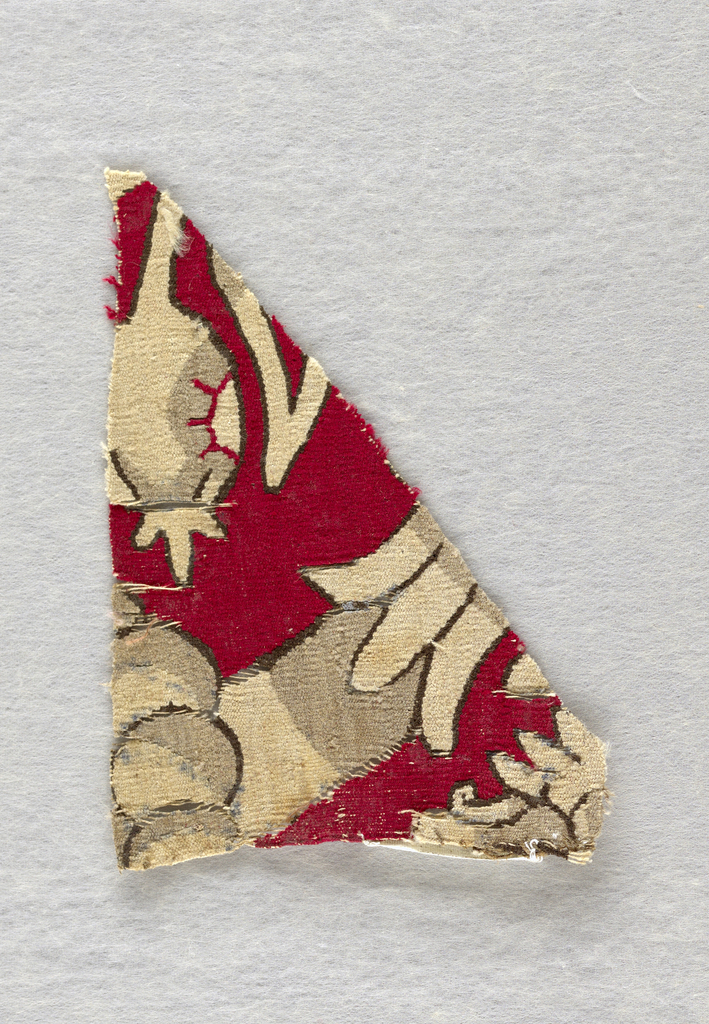 A small fragment of figured tapestry with stylized plant details on a crimson ground.