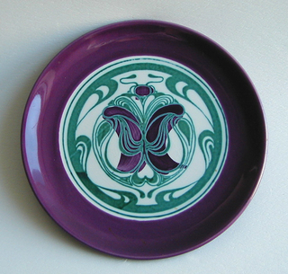 Circular form; rim with wide purple border surrounding white ground with green stylized, curvilinear decoration with passages of purple in center.