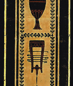 Vertical design, in black flock with red on terra cotta field. Alternating urns and musical instruments enclosed in rectangular framework formed by conventional leaf motif.