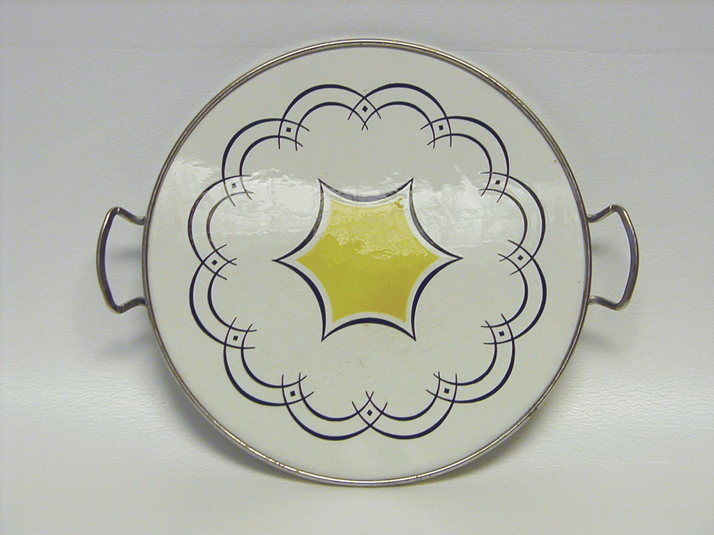 White body, rimmed in metal with two small metal handles. The design is blue half-circles that encircle a star-shape in the center that is yellow and outlined in blue.