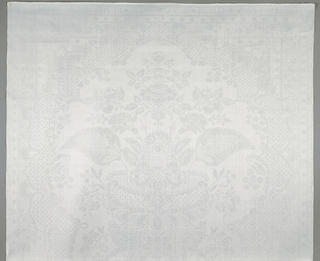 """Large-scale, vertically symmetrical pattern of flowers and leaves in the """"lace"""" style, with and ogival framing device and narrow floral borders on all four sides. """"33"""" embroidered in orange silk in the upper left corner."""