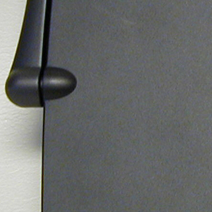 Dark grey tablet form (a) with u-shaped arm.  The arm swings up when cover is raised, allowing cover to pivot, revealing a display screen and keyboard.  Dark grey stylus (b) stored in holder under screen.