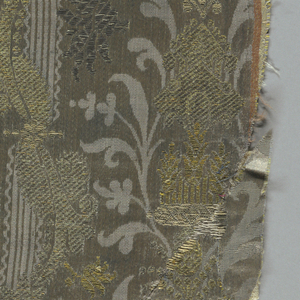 Blue-gray silk satin damasse with gold and silver metallic brocading. Vertical bands of delicate symmetrical floral decoration set off by narrow stripes, with vertical bands of floral designs in gold and silver brocading. Broad satin selvedges with pink and white stripes. Lined with red silk; edged with galloon of the period.